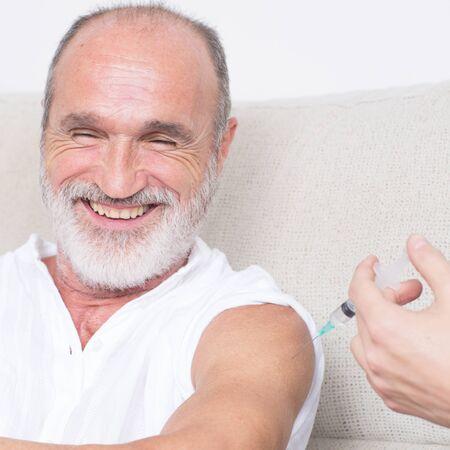 happy seniors: Happy senior man being vaccinated Stock Photo