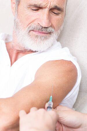 Senior man in pijn op zoek op te laten vaccineren