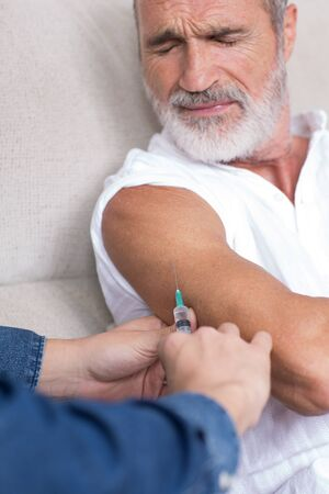 inoculate: Senior man in pain looking on being vaccinated