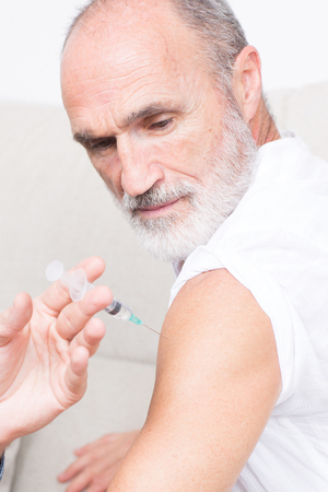 To vaccinate a senior man Stock Photo