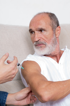 inoculate: To vaccinate a senior man Stock Photo