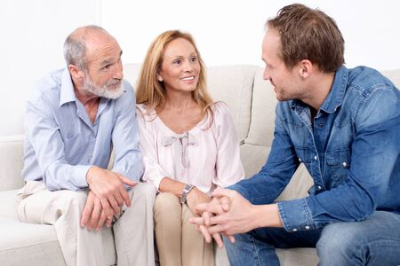 happy elderly couple talking with a younger man Stock Photo