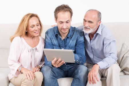 three persons: Three persons looking at a tablet Stock Photo