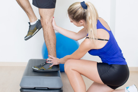 regularly: Personal coach helping with step exercise