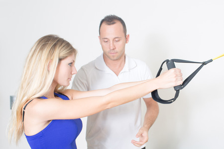 regularly: personal coach helping a young blond woman