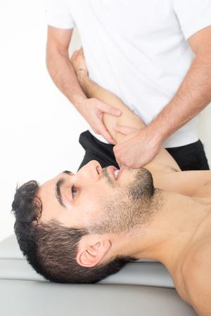 medical fight: Young sportsman enjoying massage Stock Photo