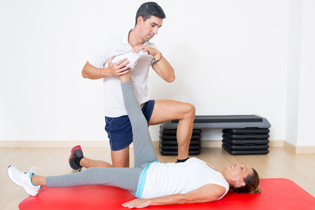 approaches: Personal trainer helping with stretching exercise