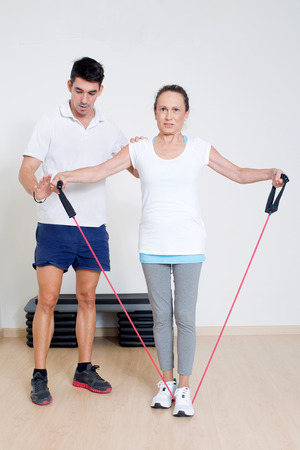 regularly: Personal trainer helping with skipping rope exercise