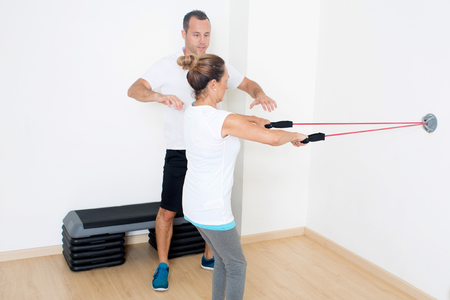 regularly: Personal trainer helping with exercise