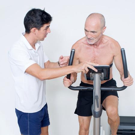 regularly: Personal trainer monitoring indoor bike