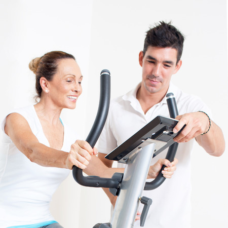 regularly: Personal trainer correcting spinning exercise of a senior woman
