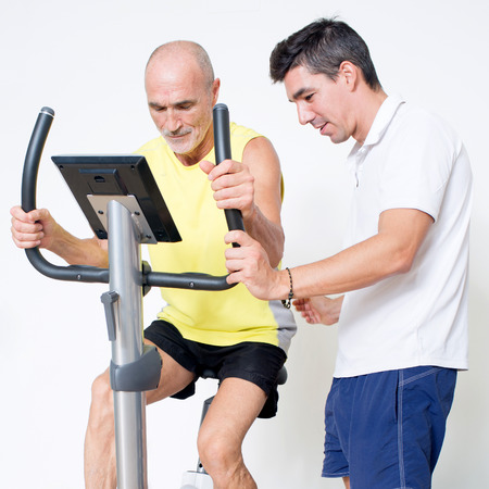 correcting: Personal trainer correcting spinning exercise