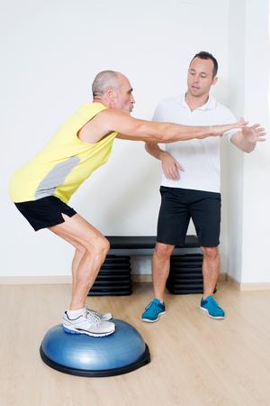 regularly: personal trainer explaining exercise on balance platform Stock Photo