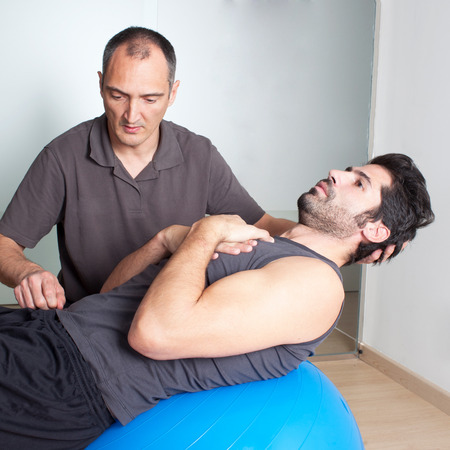 regularly: exercise on medicine ball with coach Stock Photo