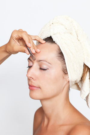 Woman's eyebrows being plucked in