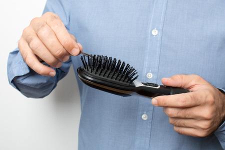 checking hairbrush for hair photo