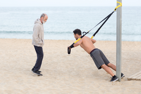 Man making trx exercise on the beach with personal trainer