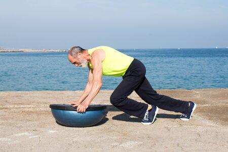lose up: Senior man making exercise on balance plattform by the sea Stock Photo