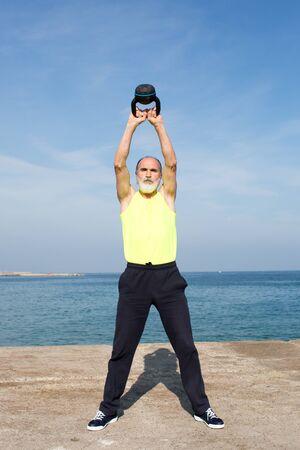 Senior man making the kettlebell exercise on the beach