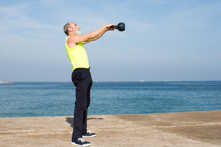Senior man making the kettlebell exercise on the beach