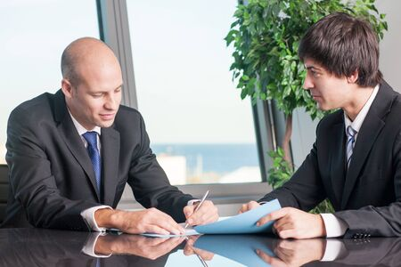 assistent: Businessman signs documents with assistent