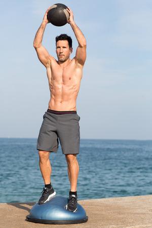 Athletischer Mann mit Medizinball auf Balancenplattform nahe dem Meer