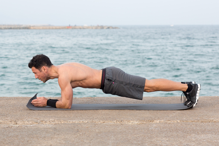 Forearm plank exercise outside close to the beach