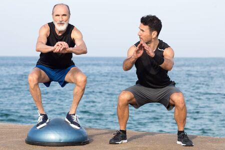 Personal coach on the beach with senior Banco de Imagens
