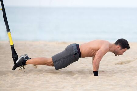 Athletic man with legs making trx exercise on the beach