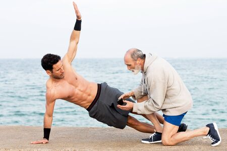Athletic Man making side plank exercise outside on the waterfront with coach Stock Photo