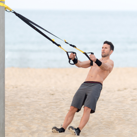 Athletic man making trx exercise on the beach Stock Photo