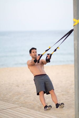 Athletic man making suspension training exercise
