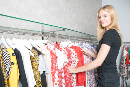 blond woman choosing clothes in a store Stock Photo