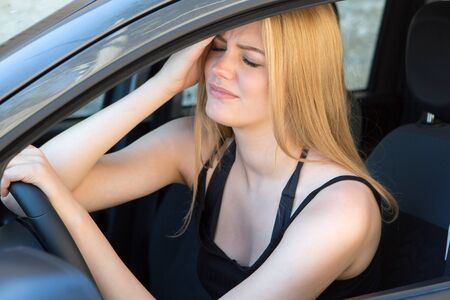 young female driver with headache in a car