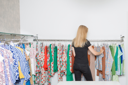 Young blond woman in a store looking for clothes Фото со стока