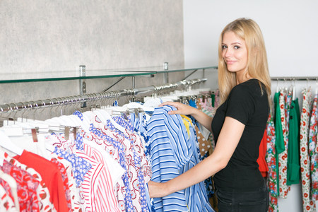 Young blond woman in a store looking for clothes Stock Photo