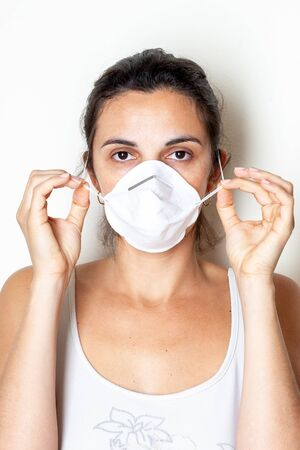 Woman putting on a protective mask because of the coronavirus