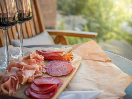charcutería: Carne curada, prosciutto en rodajas y salami. Vasos de vino tinto en la mesa. La luz del sol desde el lado.