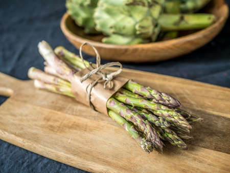 Fresh green asparagus on a wood cutting board.