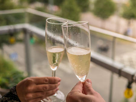 Hands Man and woman on balcony with glasses of champagne