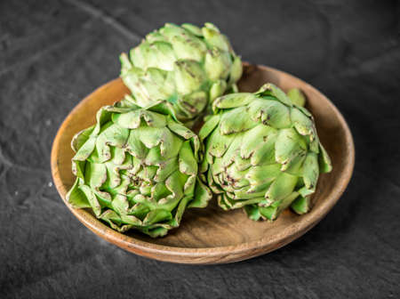Fresh organic artichoke in wood bowl on dark background.