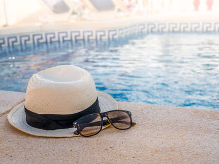 Holiday concept. A travel hat and sunglasses on the side of the pool in the summer sun. Space for copy and text in the water and light area.