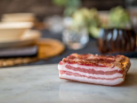 Smoked bacon on a marble board. Dinner out of focus in background. Stock Photo