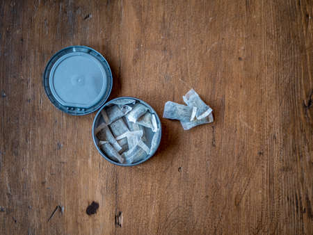 Swedish Nicotine. Portion Snus in container on wood background.