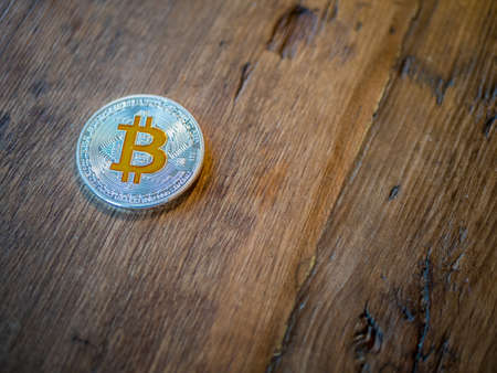 Silver bitcoin with cold details on rustic wood background.