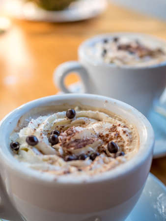 Coffee cups of cappuccino with cream and cocoa on table.
