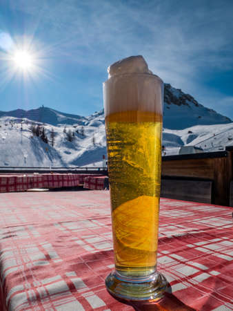 Large draft beer glass on a table in the alps. Ski hill or slope and sun light in background.