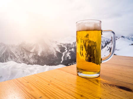 Glass or pint of a beer on a wood table on the top of the alps. Sun light is shining on the winter landscape.