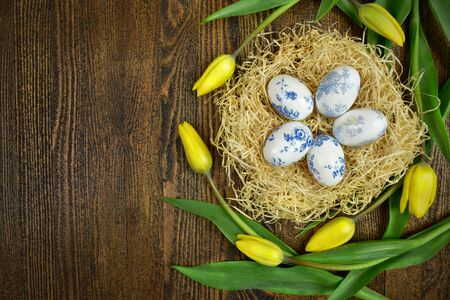 Easter decoration of eggs and tulips on wooden background