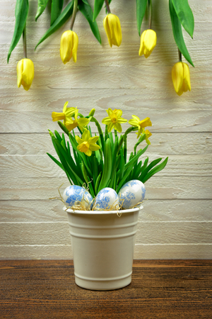 Hand painted eggs and narcissus in metal basket